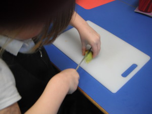 Year 1 cutting fruit using the bridge method for their fruit kebabs