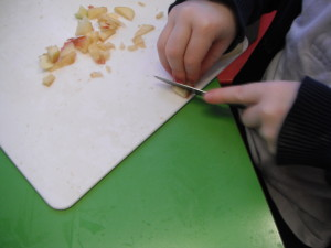 Year 1 cutting fruit using the claw hold for making a fruit kebab.